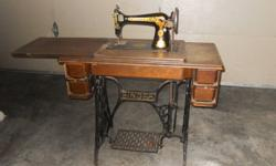 This is a steal of a deal for this 1930s antique sewing machine which is powered by a metal foot petal system that is still in working condition with original parts. The unit includes a nicely finished original wood cabinet.