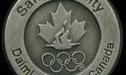 2002 Salt Lake City Daimler Chrysler Canada. This pin is in the tone of pewter with no other colors. Top of circle says Salt Lake City and bottom says Daimler Chrysler Canada. In the center of the circle is the Canadian Olympic logo maple leaf and flame