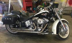 This 2005 Softtail Deluxe is in immaculate condition and has only 10000kms. The bike has Screamin Eagle stage 2 , factory hard leather bags and windshield . The bike also has an extra passenger seat and backrest as well as heated grips and a Pyle stereo