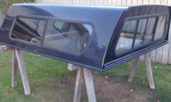 """6.5' (83"""") long black truck canopy. Was used on a 1999 Ford F-250 but should fit most trucks before the 2010 model year. Has locking latches and the hinge operates smooth and holds open. Includes sliding side windows with mesh screens. Price is $400 OBO"""