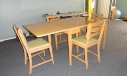 Antique 1950's Original Table and 4 Chairs. This table starts out compact and opens up, with 3 leaves to expand it to a family size dining table. Comes with 4 original chartreuse vinyl upholstered chairs, and 3 leaves.