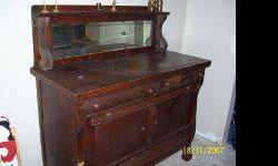 This buffet with high back mirror is made of solid oak/and oak veneer finish. This antique piece is quite unique and a rare find. It is of walnut colour and finished with flamed like design on the veneer finish. It has many drawers and two doors. This
