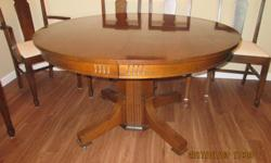 Quarter cut oak dining room table, split pedestal base with 4 extra leaves at 10 inches each. With no leaves the table is 48 inches round. includes 5 straight chairs, plus one captains chair. Crème and teal upholstered fabric seats.