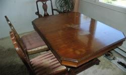 Antique mahogany table with additional leaf and six chairs (including captain's chair). Table top has some water marks but is otherwise undamaged. Solid wood chairs with well-worn original upholstery. A little TLC will make this piece a treasure! REDUCED