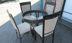 Glass, dining room table with 4 heavy, sturdy chairs Hardly used. No stains. No chips/scratches on glass. 3 feet diameter. Items are in storage and glass is wrapped so not shown in pictures. Must be able to pick up in Port Coquitlam. Paid over $800. $300