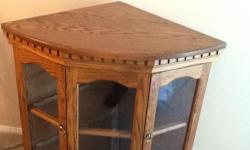 Beautiful, solid oak, lighted corner cabinet, with glass shelves. 43 inches tall, 27 inches from the corner on each side and at centre front. Cabinet is in perfect condition! Down sizing and forced to sell. Offers considered.