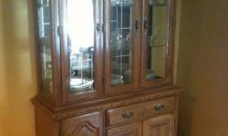 """Beautiful oak display china cabinet for sale   Light brown oak colour. Upper half has 3 glass doors with 3 glass shelves and mirrored back. Lower half has 3 cupboards and 1 drawer. Upper and lower sections can be separated for transporting.   79"""" height"""