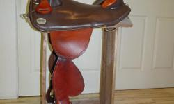 Save $ on nearly new saddle with no waiting! 15 inch seat, trail pommel, endurance leather, barb wire border tooling, fenders, leather covered/laced stirrups, trail rigging with large girth ring, custom conchos. Not suitable for high withers. Will