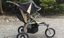 This BOB Revolution jogging stroller is black with tan trim. It has fashionable metal-spoke wheels. The front wheel can lock for jogging or can freely pivot for tight turns. It can easily maneuver with one hand and can fold up with minimal effort. This