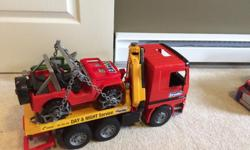 Bruder flatbed tow truck with jeep to haul on the back. Includes all the little parts.