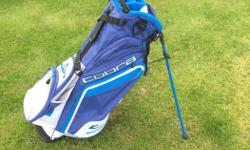 Lightweight Cobra Stand Bag. Classic Blue/Blue/White colourway. Interesting full length club divider system. Double strap, two carry handles, drink sleeve, umbrella sleeve, multiple pockets including valuables pocket. Rain hood. Lightly used.