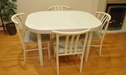 "custom made white oval kitchen table 4' X 3' with 2 14"" extensions in showroom condition.  4 chairs in grey leatherette.  2 chairs used daily for breakfast, lunch, dinner show some wear.  The other 2 chairs are in mint condition. This is a cash only,"