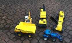 A set of five diggers. Three are metal, Tonka toys - well used but still in good shape. A metal tractor and a plastic excavator - both minimally used.