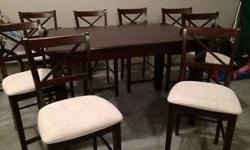 "Sturdy wood counter-height dining set includes table, leaf, 8 chairs. Leaf stores under table (butterfly mechanism). Chair seats light beige material. Table 35""H x 54"" x 36"" (no leaf) or 54"" (with leaf). Few marks on table top but otherwise in very good"