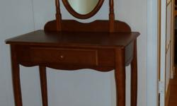 Wooden dressing table with attached oval mirror and small drawer for sale.  Beautiful chestnut coloured wood.  Curved legs.  Very pretty.  Perfect for small space since is nice sized.   Excellent, almost new condition.  $80.00 OBO  Janine 250 354-4475