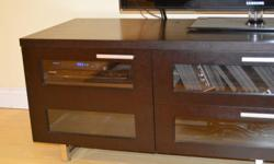 """Solid Dark wood entertainment centre 77"""" wide x 22"""" Deep x 22.5"""" High. Windowed cupboards for electronics on either end and lots of storage in centre drawers. Very solid and in excellent condition. Unfortunate does not fit in our new home. TV in picture"""