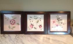 Embroidered flowers set in wood frames. Colours are pink, green and wine coloured. Sold as a set.
