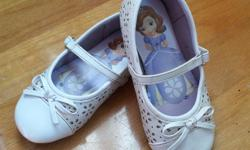 White faux patent leather shoes with silver flower detail. Disney Sophia the First branding. Skid resistant. Size 8.