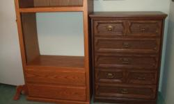 """Like new solid oak TV stand. Rolling doors to hide TV and 2 drawers with rollers. 20"""" deep 35"""" wide 58"""" high TV opening is 30 3/4"""" wide and 26 3/4 """" high. Please phone NOTE: dark dresser on right is sold."""