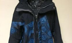 This black and blue honeycomb shell coat features attached hood with velcro tab on the back to secure ski or snowboard goggles, inside zip pocket with headphone cord access, outer zip pockets, double zip and velcro tab closure, corded hem and velcro cuffs