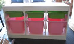 3 large pink and 3 small green plastic bins in a white laminate frame. Needs some cleaning with baking soda, but these units are durable.