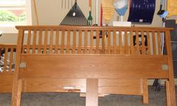 Mission style oak bed frame. Made in Canada. Headboard is 7 feet wide x 42 inches tall. Footboard is 7 feet wide x 30 inches tall. Includes side rails and slats so there is no need for a box spring support. Centre support also included. Excellent