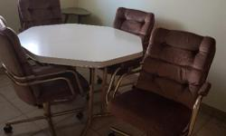White octagon table with leaf and 4 swivel tan chairs on castors