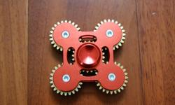 This is an all-metal spinner with bearings in the middle, and 5 gears that move together across the four arms. The centre bearing spins very well. The 5 gears turn manually and are all integrated to turn together, but do not spin the same as the centre