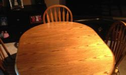 """42"""" round oak table with 4 chairs and 18"""" leaf Has some minor wear from every day use but a good solid package"""