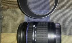This lens is still in excellent functional and cosmetic condition. It is a 4/3 lens for the E-series line of DSLRs from Olympus. It will work with the micro 4/3 mirrorless cameras from Olympus but requires an adapter (not included). Includes a lens hood.