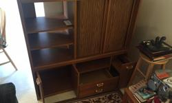 """Entertainment centre for TV, Stereo and DVD player. Drawers for DVD's etc. Some scratches and blemishes on sides but otherwise in decent condition. From non-smoking and no-pet household. Dimensions: L=49 3/4"""" W=18"""" H=48 3/4"""" Missing glass door on left"""