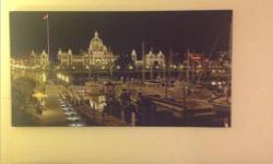 A Scenic view of the habour at night with the parliament building with the light on in the background
