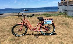 Pedego Electric Comfort Cruiser Bike Coral with blue rims 26-inch whitewall tires, step-thru frame Six speeds + throttle drive 36V 10aH battery & charger Black grips and sprung comfort seat Disc and band brakes This coral step-thru Pedego electric Comfort