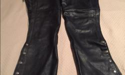 Leather King brand chaps, worn half a dozen times, small scuff on one leg (shown in picture 2). Ladies adjustable size medium, zip and snaps on outside of leg, easy to work.