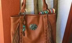 "***Lightly used Grainy leather Western handbag by ""SHYANNE "" **** *Rich color , saddle stitching , Turquoise accented Concho , turquoise bead hanging accents with feathers. * Soft Fringe flows *Excellent Travel Bag for carry on Soft bag many pockets"