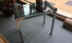 Mid Century Modern glass topped side table. Metal frame with smokey glass top. 24 W x 14 D x 22 H.