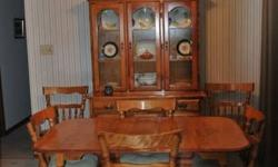Solid maple dining set.  Table with two leaves and six chairs.  Matching sideboard with 4 glass upper doors and three drawers and closed storage below.  Matching corner display unit, glass doors, one drawer and closed storage on bottom.  Must be sold as