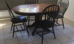 Solid oak, with a leaf, comes with 4 chairs. Chairs and table base painted a distressed black. The table top is worn but a quick sand and a coat of finish and it would look brand new!