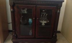 Beautiful darkly stained maple cabinet. Glass doors and shelves. An elegant statement piece and perfect for displaying those treasured items. Call or text.