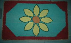 A cheerful hooked mat  (32 ins by 19 ins) has a big sunflower on a turquoise background in brick red.  The edge is bound with a floral-patterned tape. (I visit Halifax and South Shore towns often and can take this item with me to show any interested
