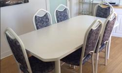 White table and 6 chairs for sale. Both the chairs and table have a white metal frame. The chairs are comfortable to sit on and have no holes in any of the material. The table is sturdy and has no stains or scratches. The table has a removable leaf in the