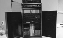 Audio system includes two - 3 way Speakers, Amplifier, dual Cassette player, turntable (needs drive belt), RCA 5 disc CD player. Includes cabinet with glass door. Must sell.