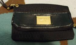 Black tommy hilfiger clutch. Has a strap for your wrist and the tommy crest on the front it opens up and there is a zipper and a button to close it.