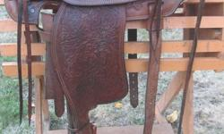 Simco model 4035, nicely tooled, brown with black seat area. Nice stirrups - leather wrapped and laced.