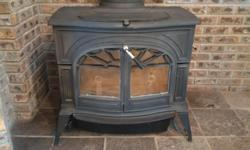 """The wood-stove is a """"Defiant - Model 1610"""" by Vermont Castings. It is approximately 18 years old and constructed of very heavy cast iron and obviously rarely used. It is in excellent condition. Stove comes with approximately five feet of 6"""" pipe connected"""